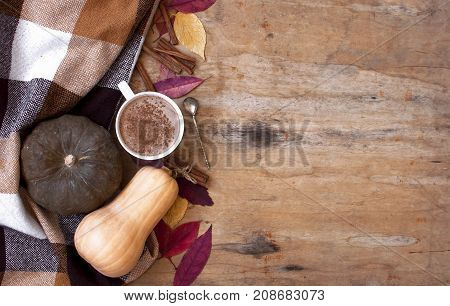Rural wooden background with pumpkin and autumn leaves, a cup of pumpkin latte with coffee or cocoa, a notebook, a plaid in a cage, top view with copy space. Autumn background.