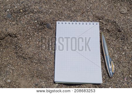 Open white note book on rings with metal ball pen on the sandy beach