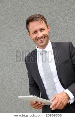 Businessman using electronic tablet leans against wall poster
