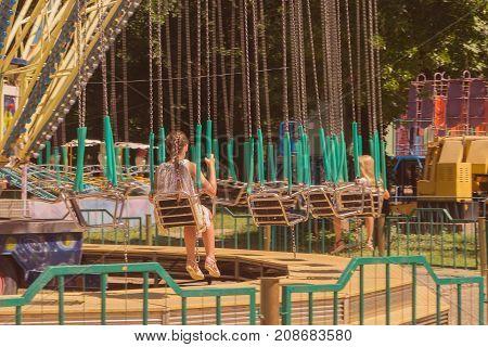 Simferopol Crimea Russia August 01 2017: Chain swing carousel in the park witn a little girl sitting on the seat