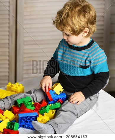 Kid builds of plastic blocks. Childhood and educational activities concept. Toddler with curious face plays with colorful bricks. Boy plays with lego on wooden wall background defocused