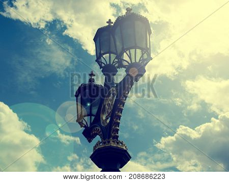 Vintage color toned old street lamp with lens flare on summer sky