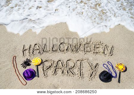 Halloween Party background with candies spider and hats on the sandy beach near the ocean