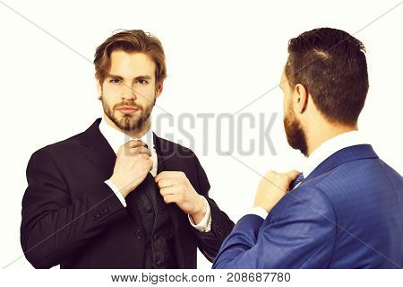 Businessmen In Blue And Black Suit Tying The Necktie