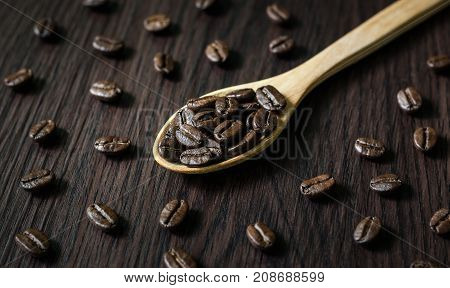 Roasted Arabica coffee beans in the wood spoon