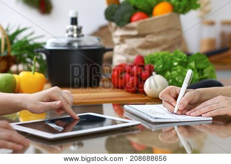 Close-up of  human hands are gesticulate over a tablet in the kitchen. Friends having fun while choosing menu or making online shopping.