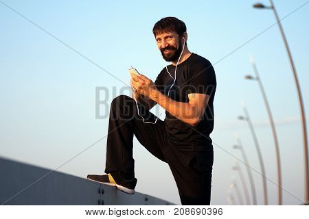 The smiling bearded man with earphones is using phone outdoor.