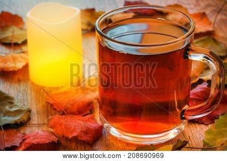 Glass cup of tea and glowing candle on wooden table with autumn leaves. Warm toning. Selective focus