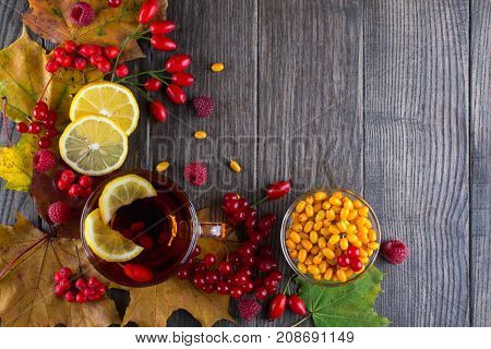 Autumn healthy beverages concept. Cup of tea with autumn berries sea buckthorn,  viburnum, rose hip, rowan and fall leaves. Drink with vitamin c. Flat lay