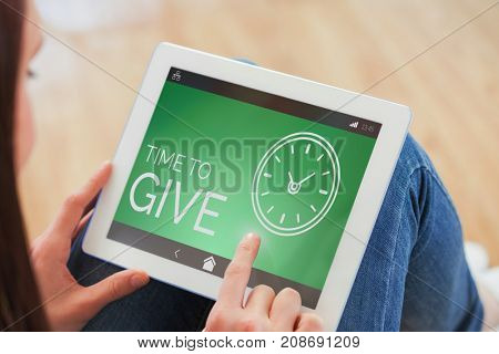 Teen using a tablet pc sitting on the floor against time to give text with clock icon on green screen
