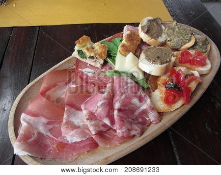 Typical rustic tuscan appetizer with crostini prosciutto brawn salami cheese on a wooden tray . Italian starter
