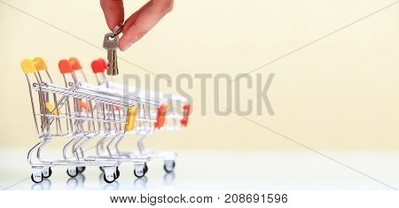 Real estate services concept. Hand put keys into shiny shopping trolley. Copy space at the right. Banner for real estate services theme.