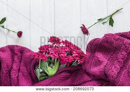 Knitted accessories and burgundy chrysanthemums on a white wooden background