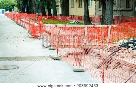 Construction site safety net fence as barrier parallel with the pipeline trench on the street in the city