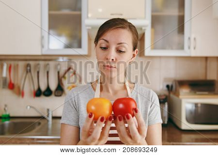 A Young Attractive Pensive Woman In An Apron Decides To Choose A Red Or Yellow Tomato In The Kitchen