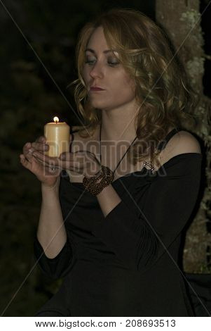 red-haired girl in a black dress holds some magical rite in the forest with a book and candles