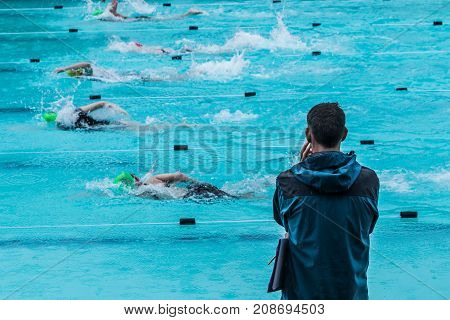 male swimming coach standing by the swimming pool in the rain watching swimmers racing by good for coaching or training concept