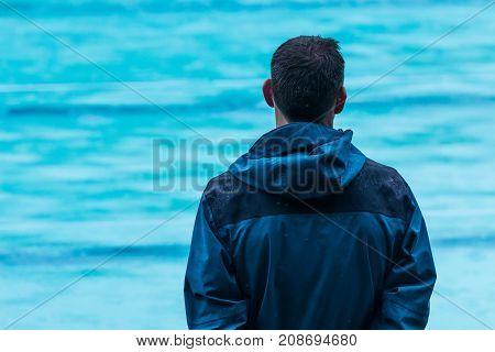male swimming coach standing by the swimming pool in the rain waiting for the rain to stop selective focus with blurred swimming pool in background good for sport or patient theme