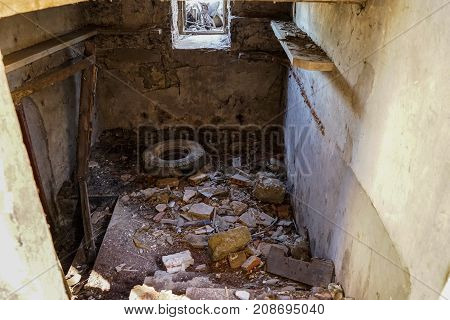 Tire tractor in a room in ruins with a window and shelves
