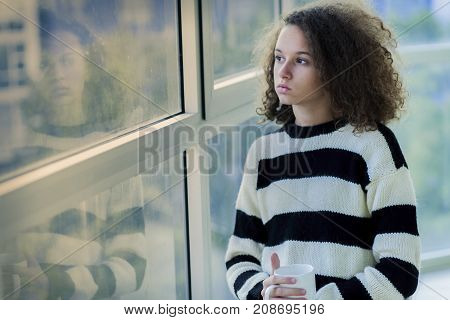 Serious Teenage Girl Sitting By The Window