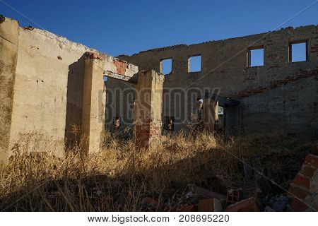 Big wall with windows and columns in ruins.