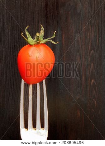 A cherry tomato on a fork on a dark background. Concept of healthy nutrition