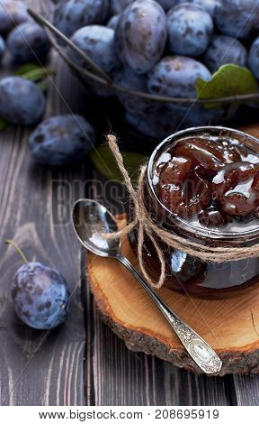 Homemade plum jam in a glass jar and fresh blue plums in a bowl on a dark rustic wooden background top view.