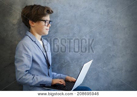 Teen Boy Wearing Glasses Sitting And Using Laptop