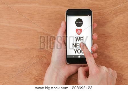 Vector image of We Need You text with icons against hands using smart phone