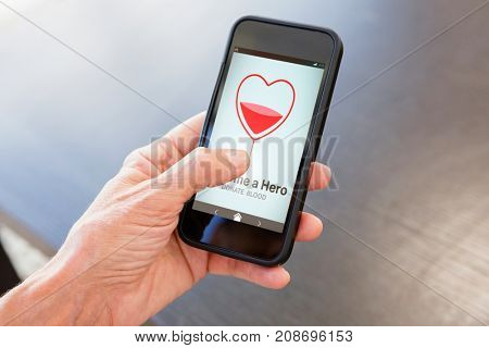 Become a Hero text with heart shape on screen against cropped image of hand holding smart phone
