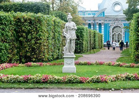 TSARSKOYE SELO, SAINT-PETERSBURG, RUSSIA - OCTOBER 7, 2017: People in The Catherine Park near The Grotto Pavilion. Foreground is the Sculpture Allegory of Amor de la Patria (Love to the Motherland)