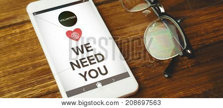 Vector image of We Need You text with icons against high angle view of cellphone and eyeglasses