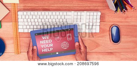 We Need your Help text with various icons on screen against businessman holding digital tablet while sitting at computer desk