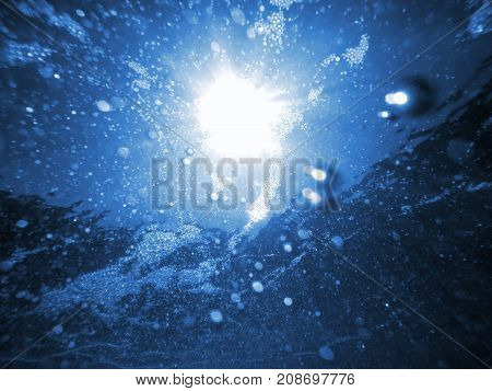 Underwater sea bubbles and foam with sunlight rays natural background