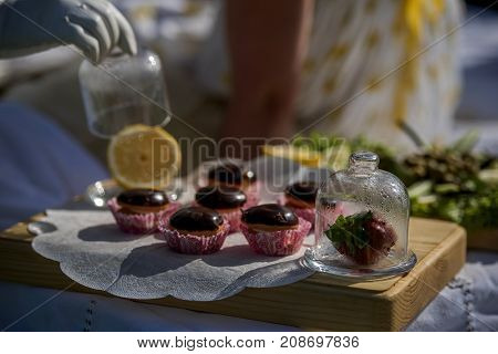 Sweet tartlets with filling and chocolate icing on a wooden plate.