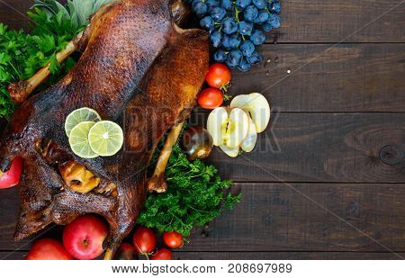 Goose baked in the oven with apples and grapes. Christmas goose on a wooden background. Festive dish. Top view.