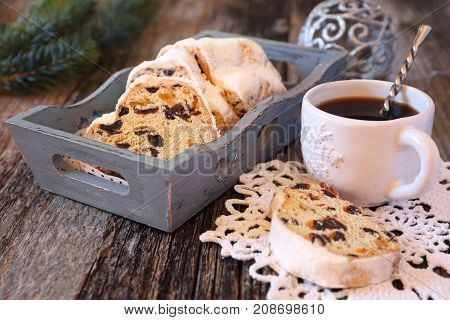 Stollen traditional Christmas cake and cup of coffee. Toned image