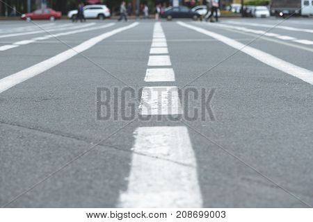 Horizontal shot of a markings on the road against the background of the people in the blur