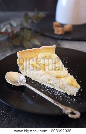 Banana coconut shavings tart on black plate