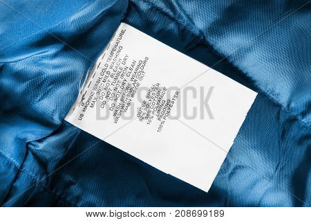Fabric composition and washing instructions clothes label on blue textile background