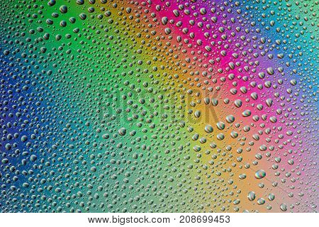 Horizontal shot of the misted glass the drops closeup on rainbow colored background