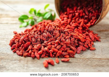 Red dried goji berries on wooden table