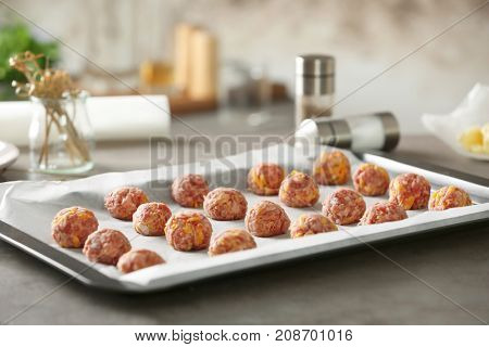 Baking tray with sausage cheese balls on table
