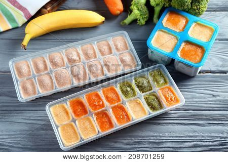 Ice trays with frozen vegetable and fruit puree on wooden table