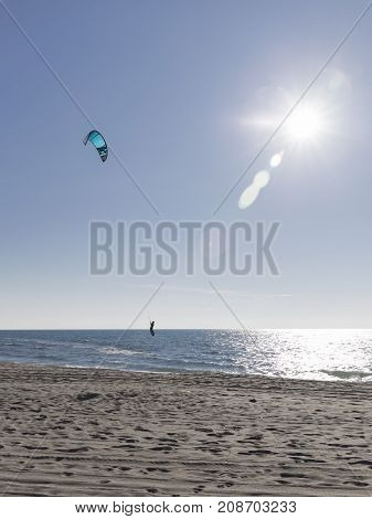 The unrecognizable kitesurfer rides on sea water on a board with a blue kite in the bright light of the evening sun and glare on the water