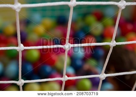 A safety net close up in children indoor playground ball pit in the background