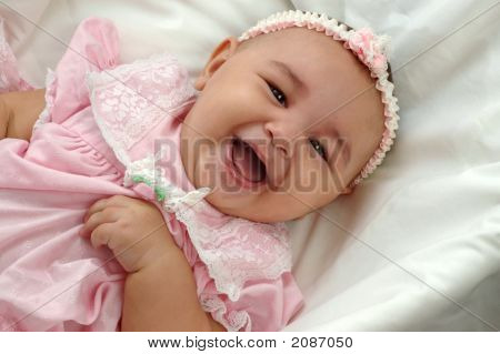Cute Baby Girl In Pink Laughing