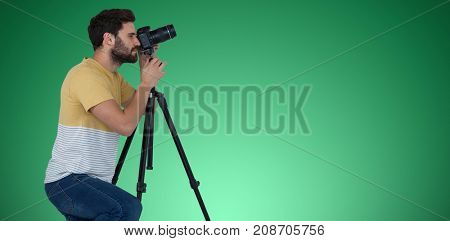 Full length of photographer photographing through camera while kneeling against green vignette