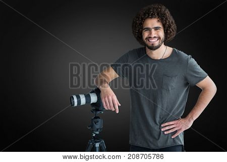 Portrait of happy male photographer with camera and tripod  against grey vignette