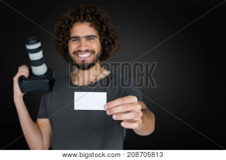 Portrait of smiling male photographer showing card while holding camera  against grey vignette